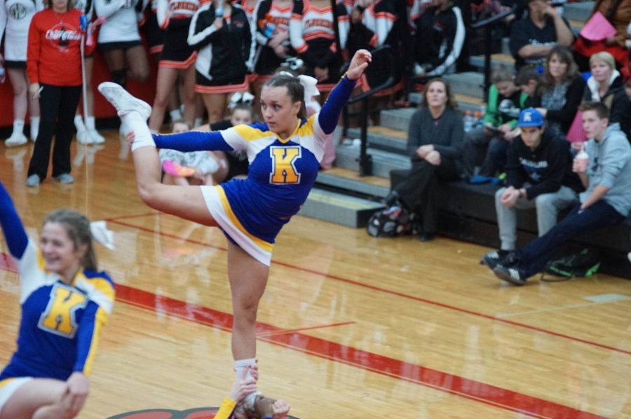 Senior Katelyn Alburtus cheers with her team at a competition in Grand Blanc.