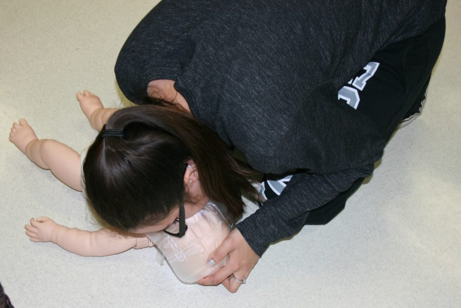 Senior+Victoria+Bond+practices+giving+breaths+for+an+infant+during+CPR+training+on+Thursday%2C+April+20.