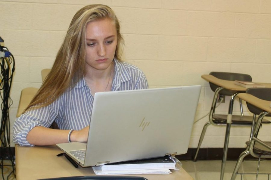 Senior Hannah VanOoteghem works on her laptop computer. The first time she used the computer, a hacker infiltrated it.