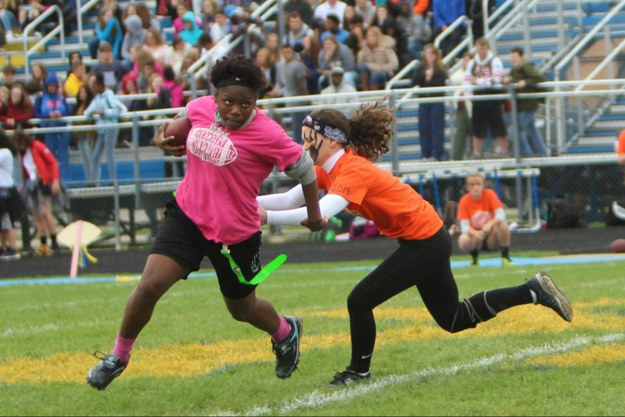 Sophomore JaKeira Wash works to elude junior Madeline Raysin in the second half of the powder puff championship Thursday, Oct. 12.