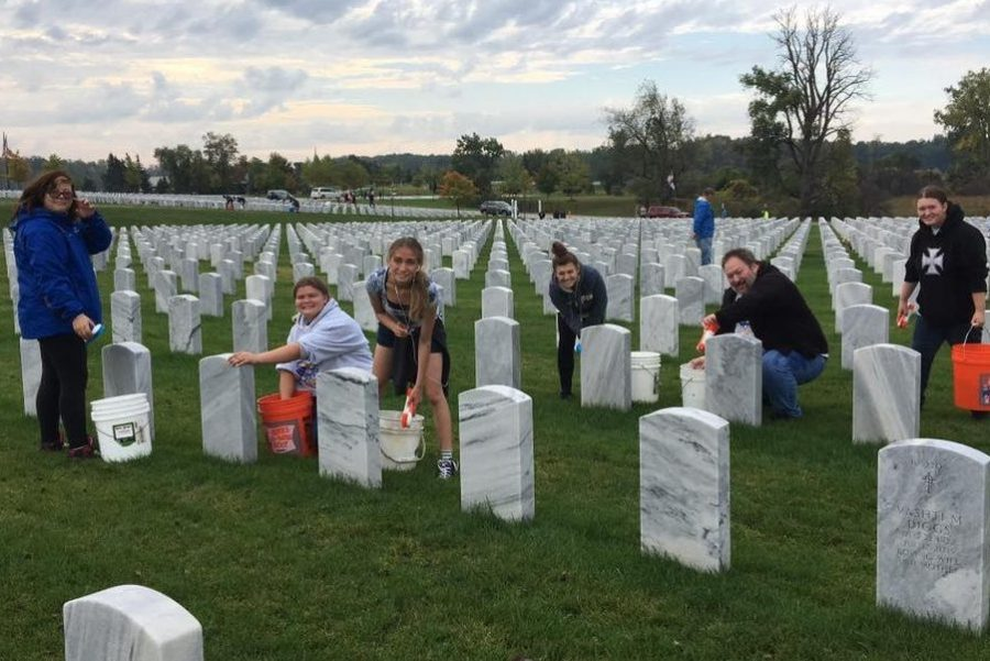 Students from the Hybrid Hornets robotics team work hard cleaning headstones at Great Lakes National Cemetery in Holly on Oct. 7.