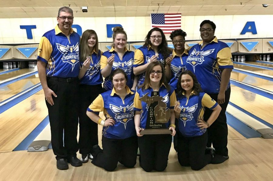 The girls bowling team shows off its championship trophy after its MHSAA Division 2 regional Friday, Feb. 23 in Bay City.