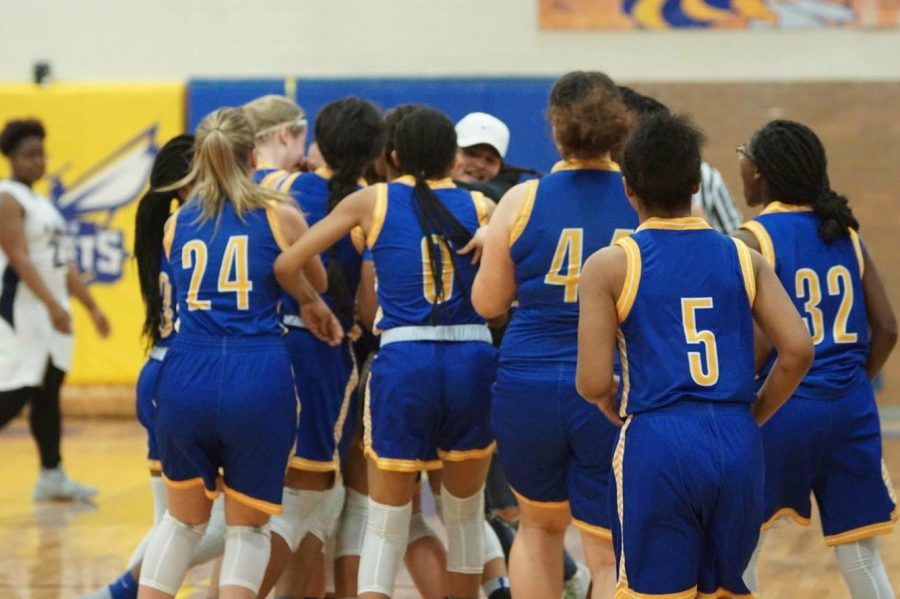 The+girls+basketball+team+celebrates+a+come-from-behind+victory+against+Saginaw+Arthur+Hill+on+Wednesday%2C+Feb.+28.+The+game+was+an+MHSAA+district+semifinal.