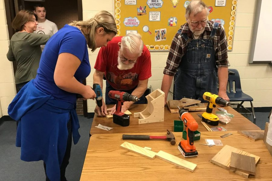 Liberty Anderson, eighth-grader, (left) learns to make a birdhouse with members of the Eastern Michigan Woodworkers at Kearsley High School, Wednesday, June 6.