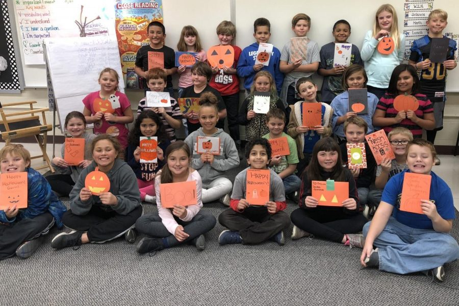 Fiedler students in Mrs. Rae Puffer's class smile with the cards from Ms. Diane Hunt's psychology classes.