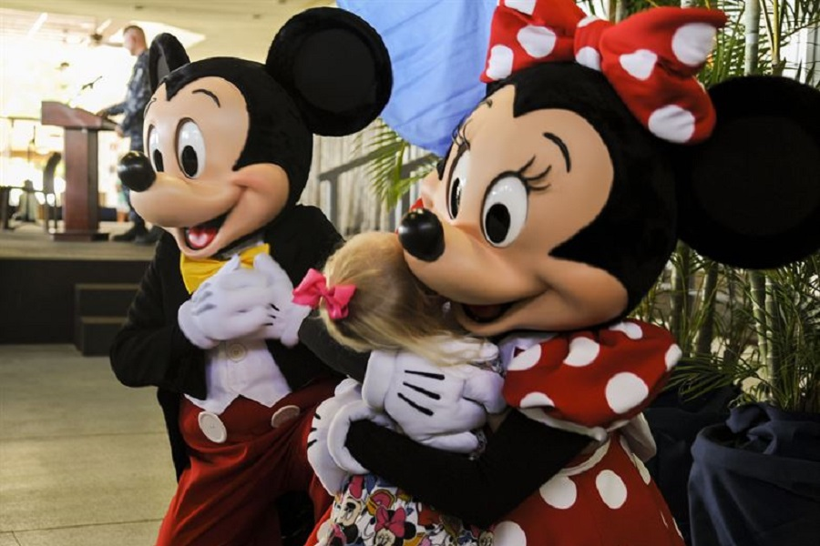 A little fan receives a hug from Mickey and Minnie Mouse during the