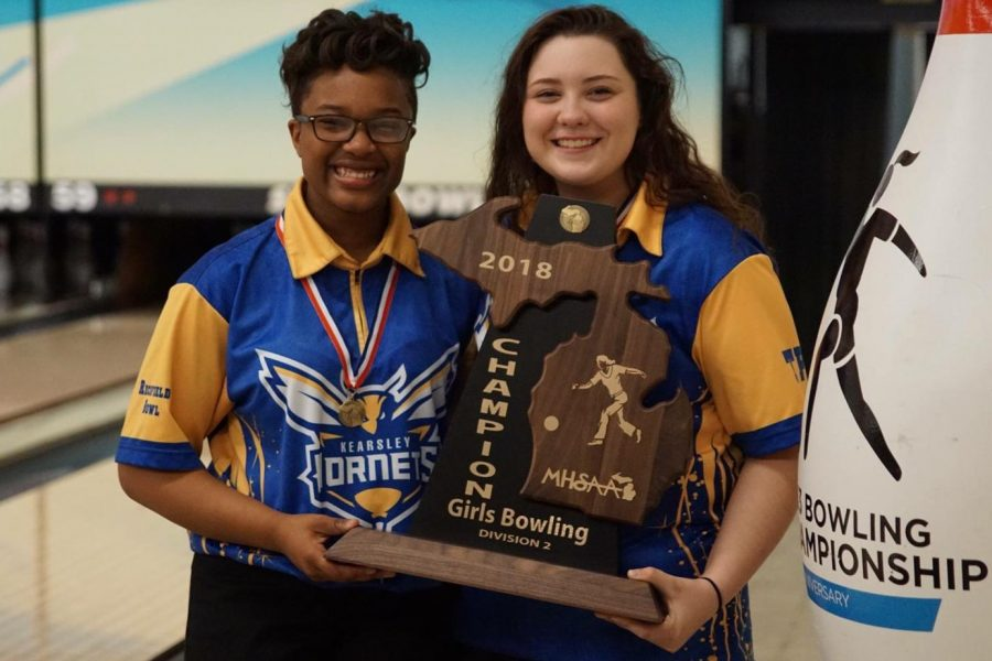 Junior Imari Blond (left) and senior Alexis Roof  hold the state title trophy from 2018.