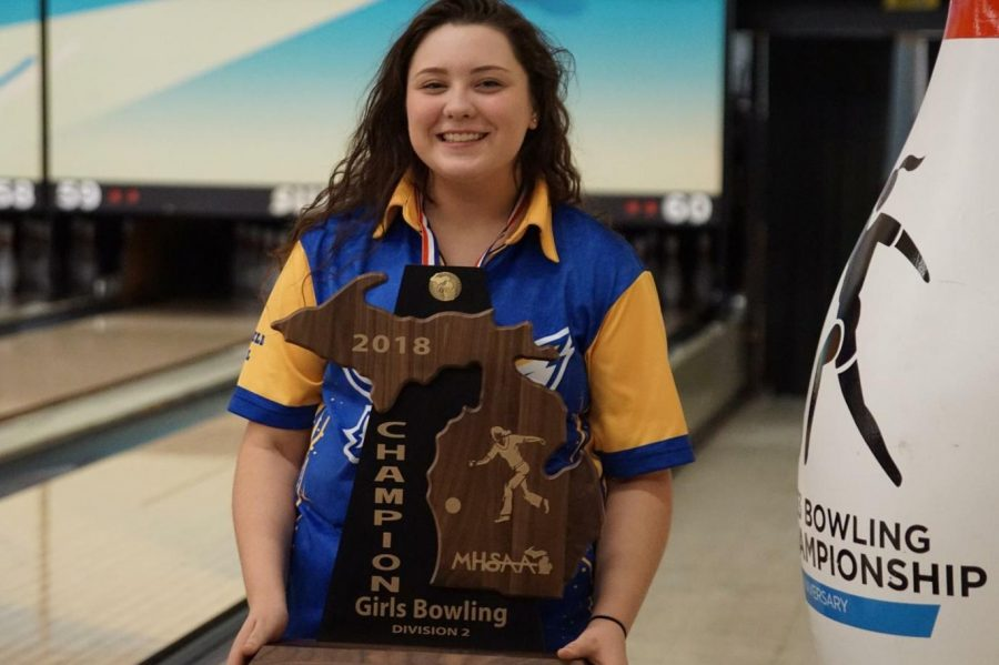 Senior Alexis Roof smiles as she holds the 2017-18 team state title trophy, her third in a row.