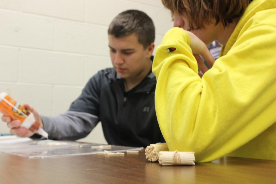 Seniors Kyle Langworthy and Nathan Maxwell glue matchsticks to build the base of their bridge