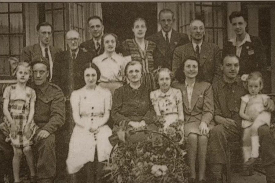 Ms. Anneke Burke-Kooistra poses with her family and the eight Jewish refugees they hid on May 5, 1945, after World War II ended.