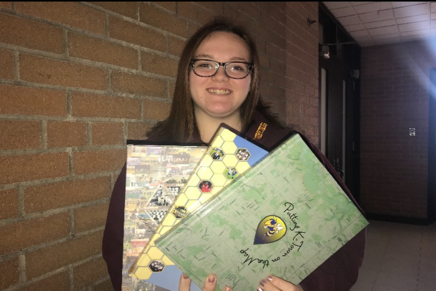 Junior Kasey Palmer, co-editor in chief, shows previous yearbook covers. For $70, buyers this year will receive two hardcover books, one of which will be given out in May.