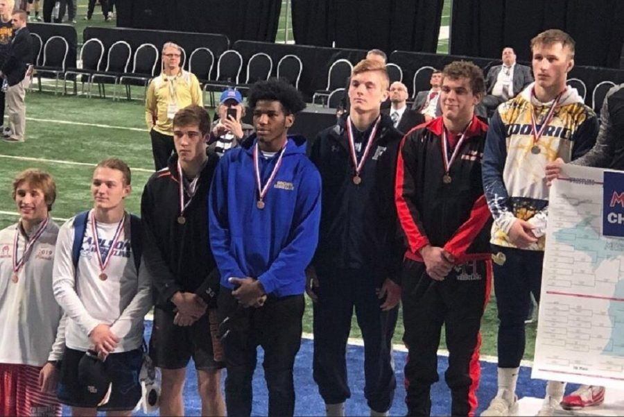 Junior John Brown (royal pullover) receives his All-State medal for wrestling after placing fifth in the 171-pound weight class during the MHSAA Division 2 individual wrestling state final Saturday, March 2, at Ford Field.