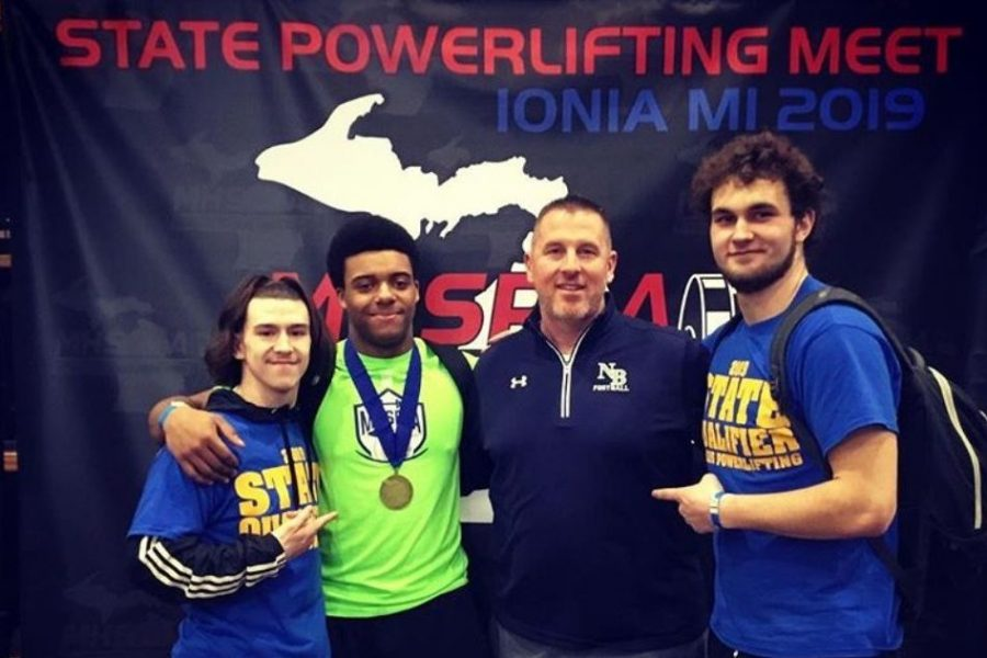 Senior Eddie Harris (second from left) celebrates with teammates -- senior Dylan Buschur (left) and junior Matthew Mcginnis (right) -- and his former football coach, Mr. Jeremy Furman, after winning a powerlifting state title in Ionia on Saturday, March 9.
