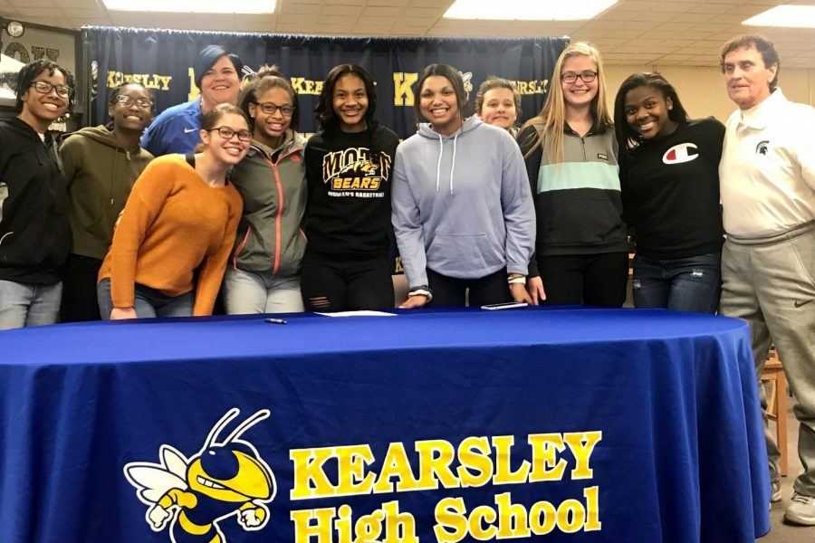 Senior Zaria Mitchner (middle with black shirt) poses with her teammates and coaches after signing her National Letter of Intent with Mott Community College to play basketball.