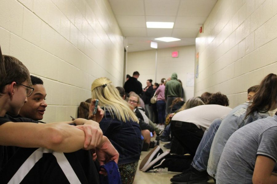 Students and parents take cover in the hallways surrounding the auditorium Thursday, March 14, as a tornado warning interrupted Foreign Language Variety Night.