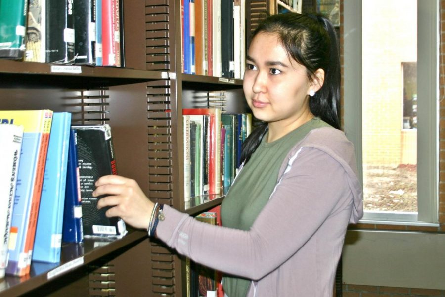 Senior Datkaaiym Talieva checks out a book in the library.