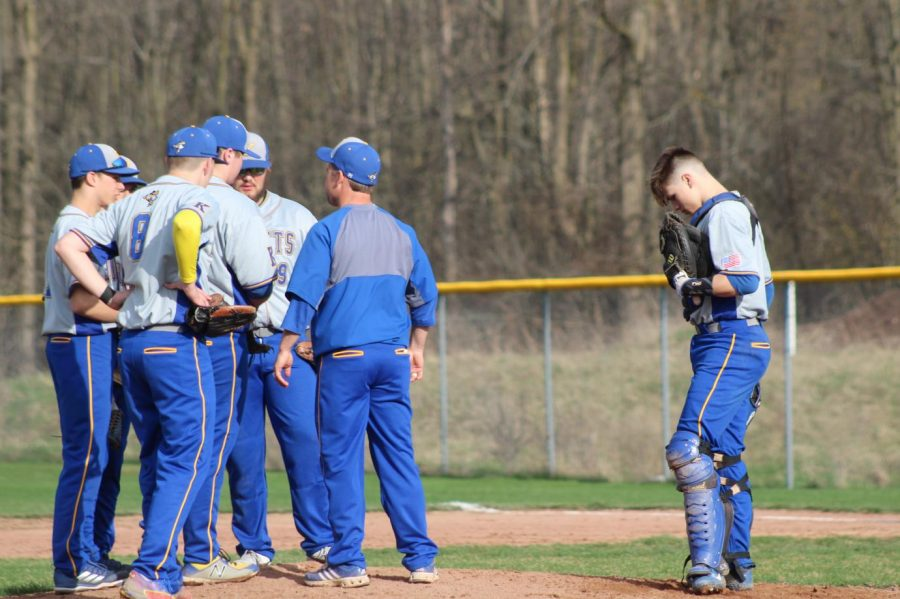The baseball team huddles up at the mound during its doubleheader against Clio on Monday, April 22.