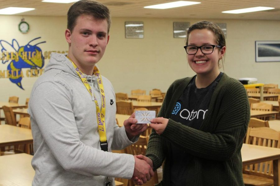 Senior Hunter May (left) won first place in the Eclipse March Madness Challenge and received a $10 gift card to a local restaurant, which was presented to him by The Eclipse editor in chief Jenna Robinson.