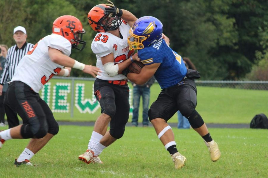 Junior Isaiah Stiverson shoves off a Fenton defender in a 35-13 loss to the Tigers on Saturday, Sept. 28. The teams played the game on over two days due to lightning delays on Friday, Sept. 27.