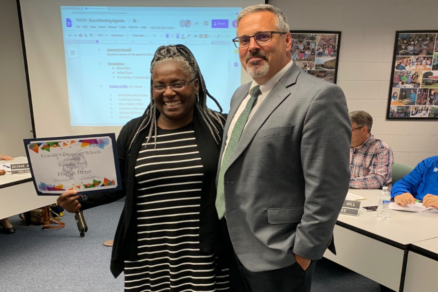 Mrs. Lachelle Pool (left) receives the September Hornet Hero award from Mr. Kevin Walworth, superintendent, during a Board of Education meeting at the administration building Monday, Sept. 9.