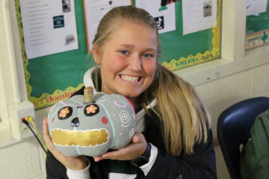 Junior Cathlyn Healy holds up her Dia de los Muertos pumpkin. Spanish IV and V students painted pumpkins to celebrate the Day of the Dead.