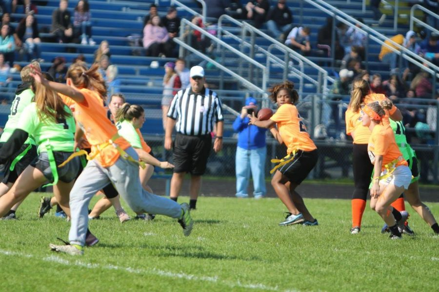 Senior JaKeira Wash (center) looks downfield at senior receiver Alexis Echols (second from left) who motions for the pass in the powder puff championship game Wednesday, Oct. 9, at KHS.