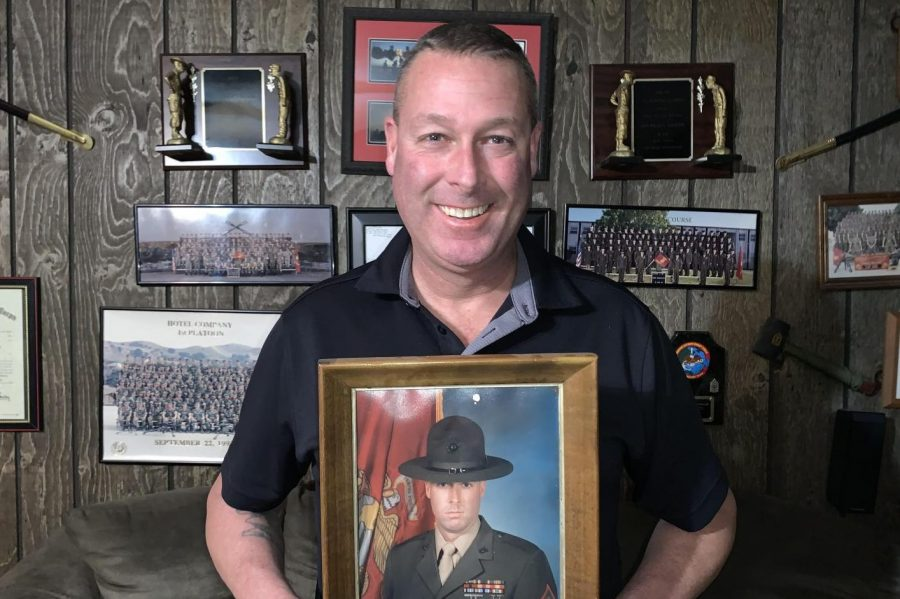Mr. Willis Atkinson, retired master gunnery sergeant, holds his drill instructor graduation portrait in front of a wall of his military accomplishments.