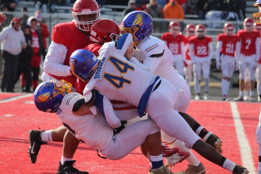 Junior Isaiah Stiverson (No. 2), senior John Brown (No. 44), and a Hornet teammate deliver a tackle on an Orchard Lake St. Mary's player in an MHSAA Division 3 district game Saturday, Nov. 9.