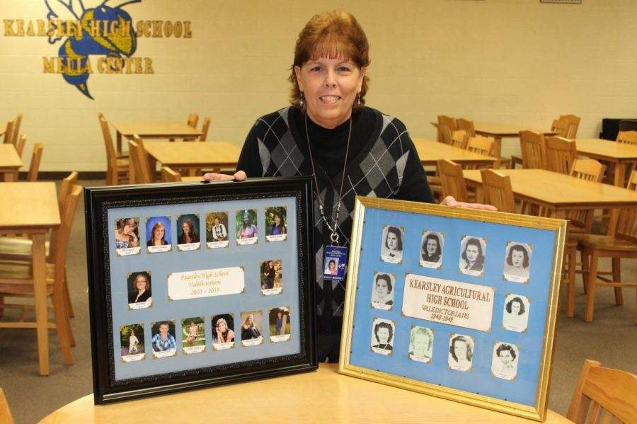 Mrs. Sally Brandt compares a new valedictorian frame (left) with an old valedictorian picture frame (right). The frames will remain in front of the main office.