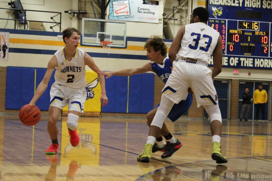 Senior Gequez Pano (No. 33) sets a pick on a Lake Fenton defender as sophomore Tyler Csintyan (No. 2) drives to the basket in a boys basketball game Tuesday, Dec. 10.