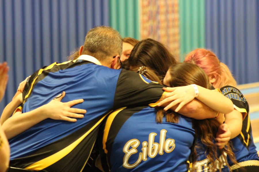 Members of the girls bowling team hug each other after junior Emilea Sturk finished the Hornets' 300 Baker game Saturday, Dec. 14.