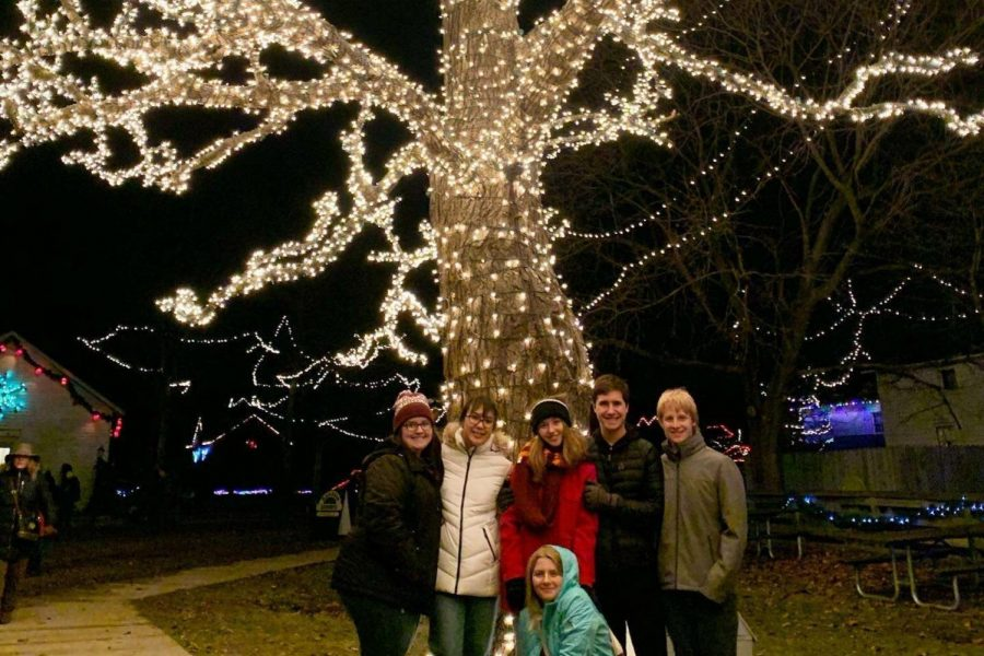 Sophomores Brooklyn Willhoite (l to r), Aizya Sorensen, Molly Gunn, Zoe Dustin, Jack Young, and Brodie Dustin huddle in front of a tree covered in lights at