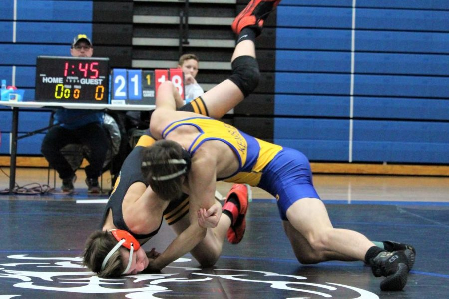 Junior Jason Judd (blue and yellow) rolls his Flushing opponent to his back to pin him at a wrestling meet in Lake Fenton Wednesday, Jan. 8.