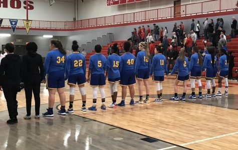 The girls basketball team links up for the national anthem before a 52-44 victory over Holly Friday, Jan. 17.
