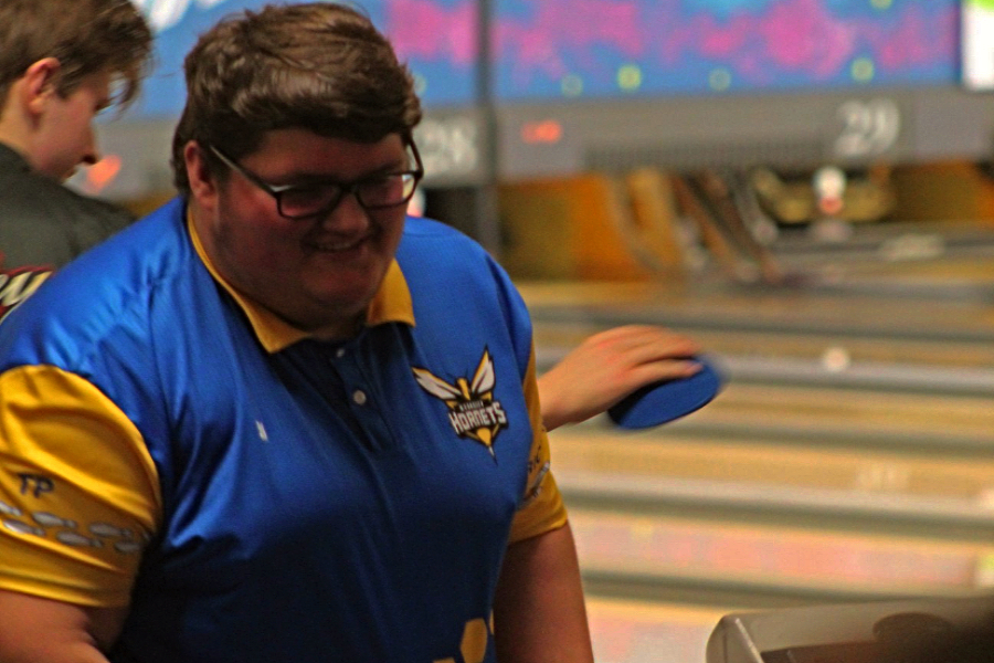 Sophomore Gage Slagor smiles toward his teammates at a bowling match. Slagor has bowled since elementary school.