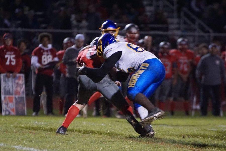 Senior Amari Douglas (No. 66) tackles a Holly ball carrier in a Metro League football game.
