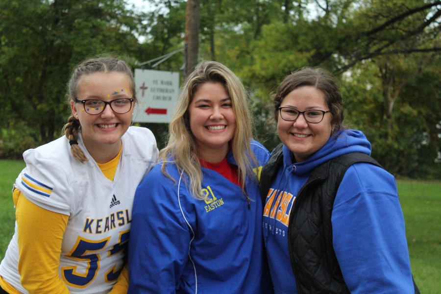 Sophomore Angel Truax (l to r), alumni Isabelle Easton, and junior Emma Cronkright posing during the homecoming parade, enjoying time with her friends.