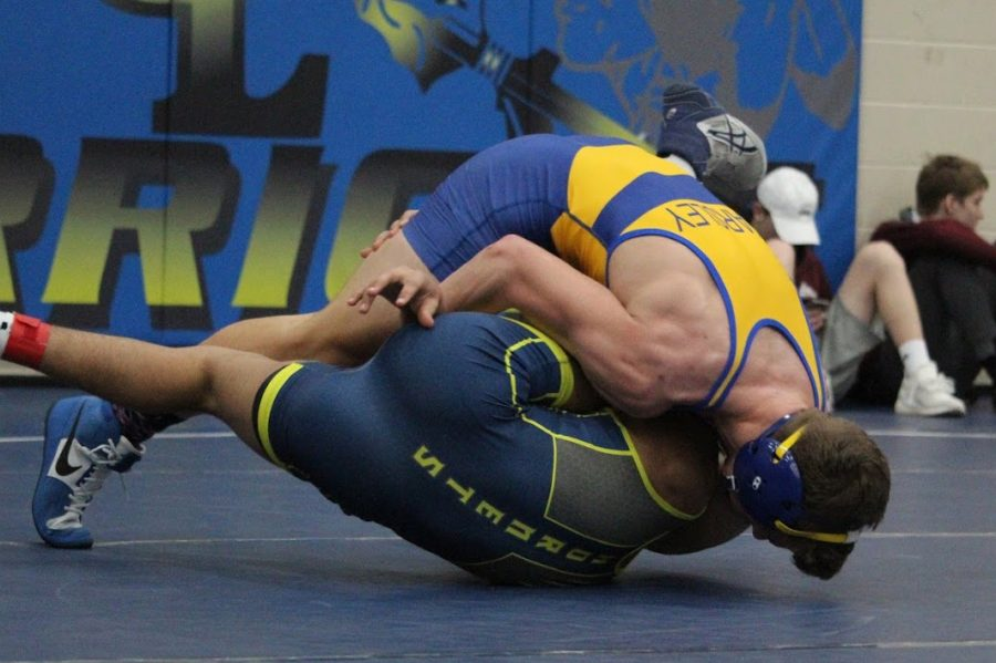Senior Trenton DiGenova top) cradles his opponent at  the Grass Lake Individual Tournament Saturday, Feb. 1.
