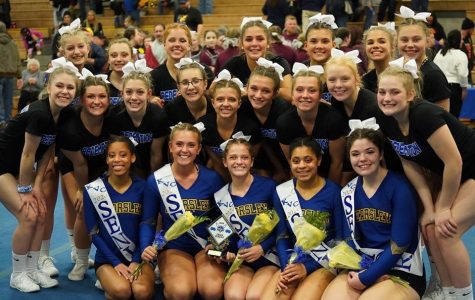 The competitive cheer team smiles as its senior night comes to an end. The Hornets took second at the Kearsley Invitational tournament Saturday, Feb. 1.