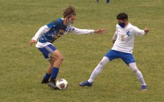 Junior Cy Cooper (left) keeps the ball away from an Imlay City player Monday, Oct.19.
